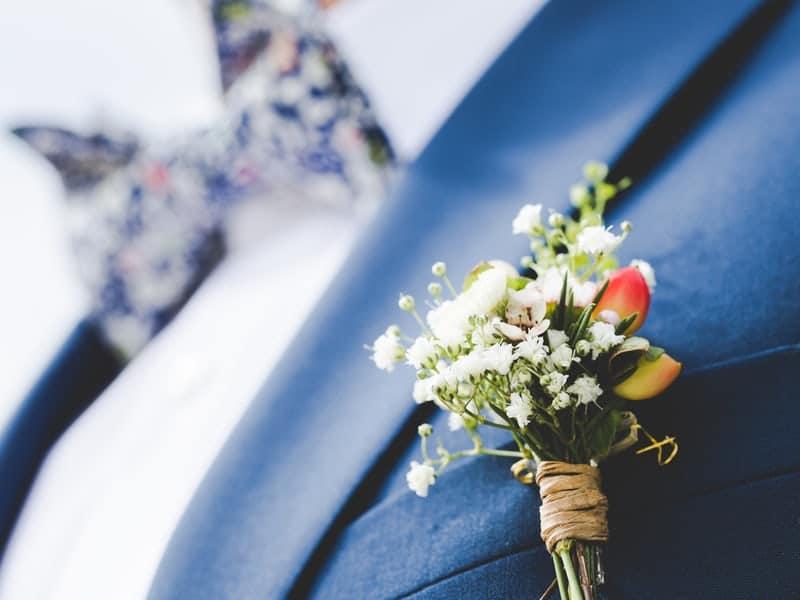 Bouquet fleuri attaché à la veste de costume du marié