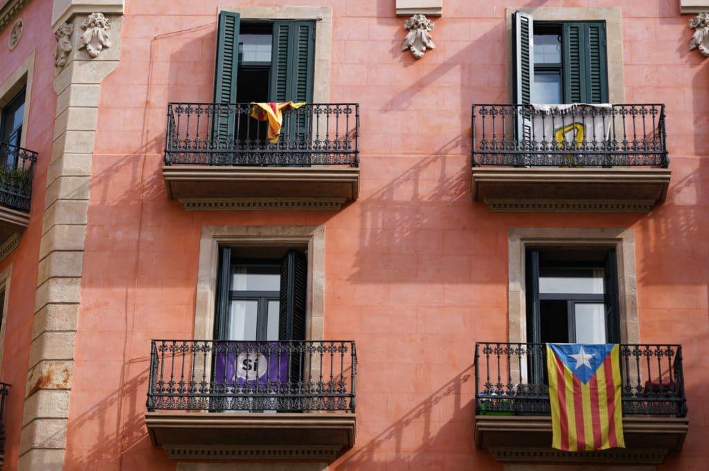 Vivre et travailler depuis Barcelone : devanture de maison rose avec drapeaux espagnols à la fenêtre