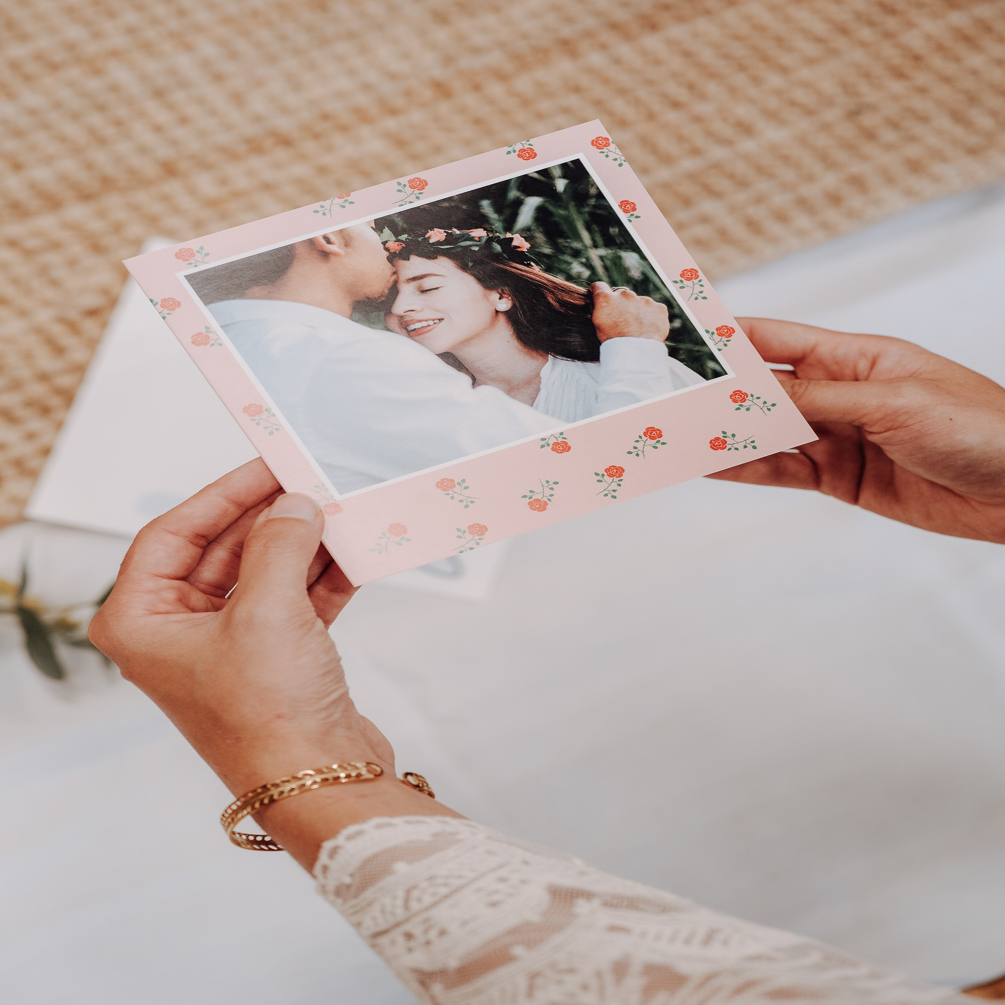 hands holding a card with couple picture