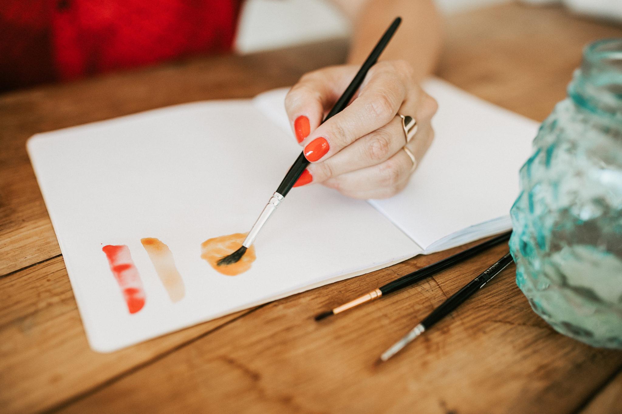 mains de femme dessinant aquarelle sur carnet