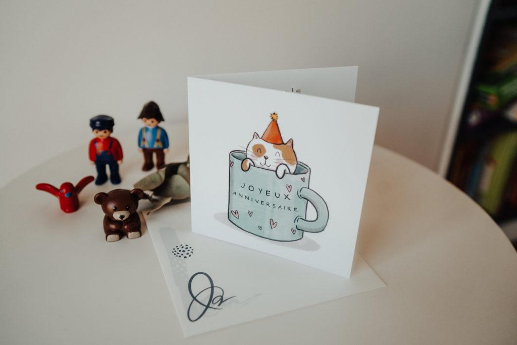 carte anniversaire avec chat dans tasse et jouets playmobil