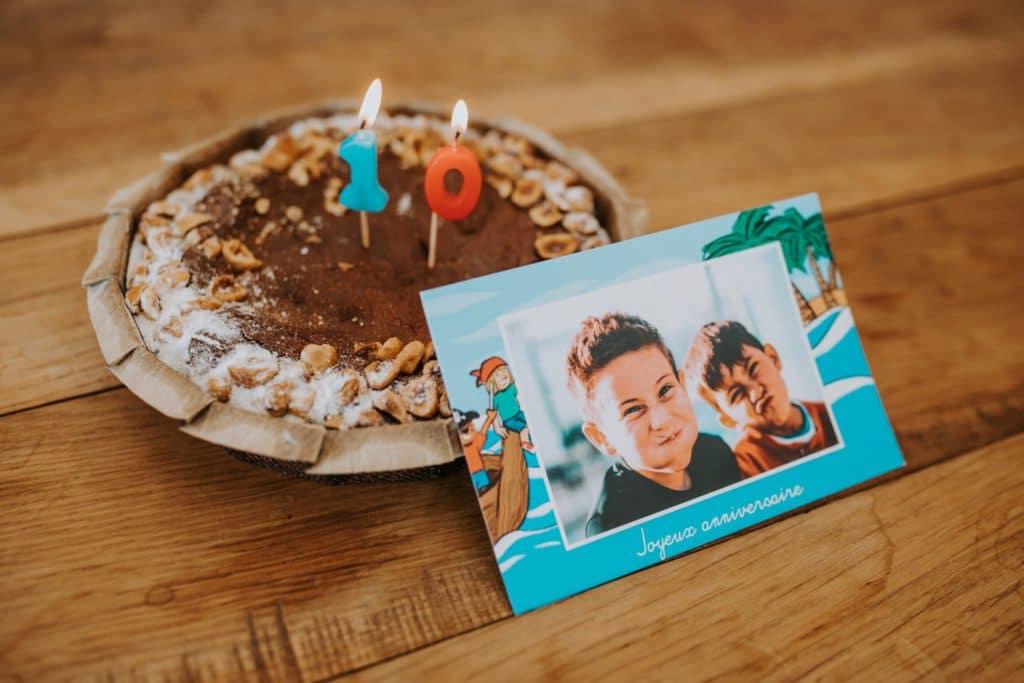 carte anniversaire enfant devant gâteau au chocolat