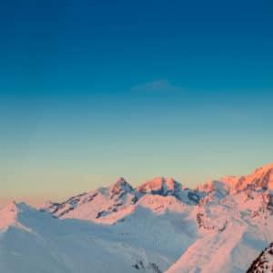 coucher de soleil sur montagnes enneigees
