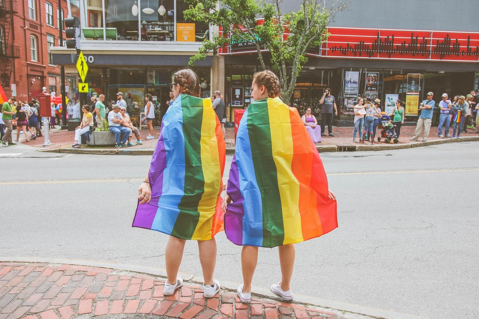 Deux femmes vêtues d'un drapeau arc-en-ciel pour la gay pride.
