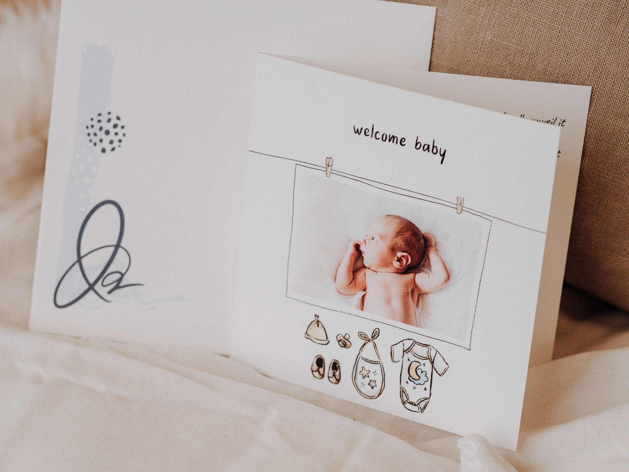 announcement card with baby clothes saying welcome baby