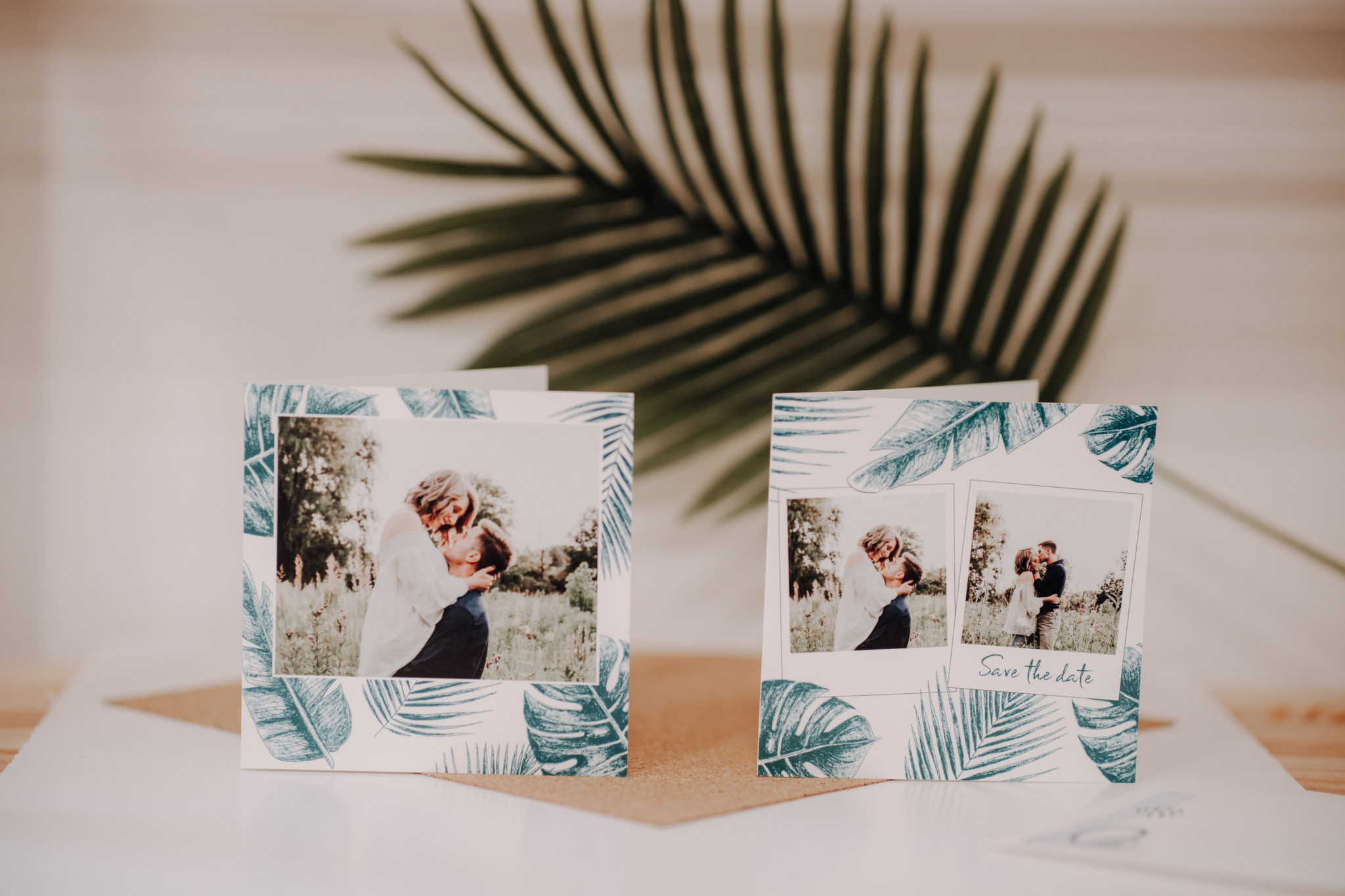 wedding invitations placed before palm leaf