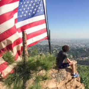 Jimmy, digital nomad chez Fizzer devant un drapeau américain