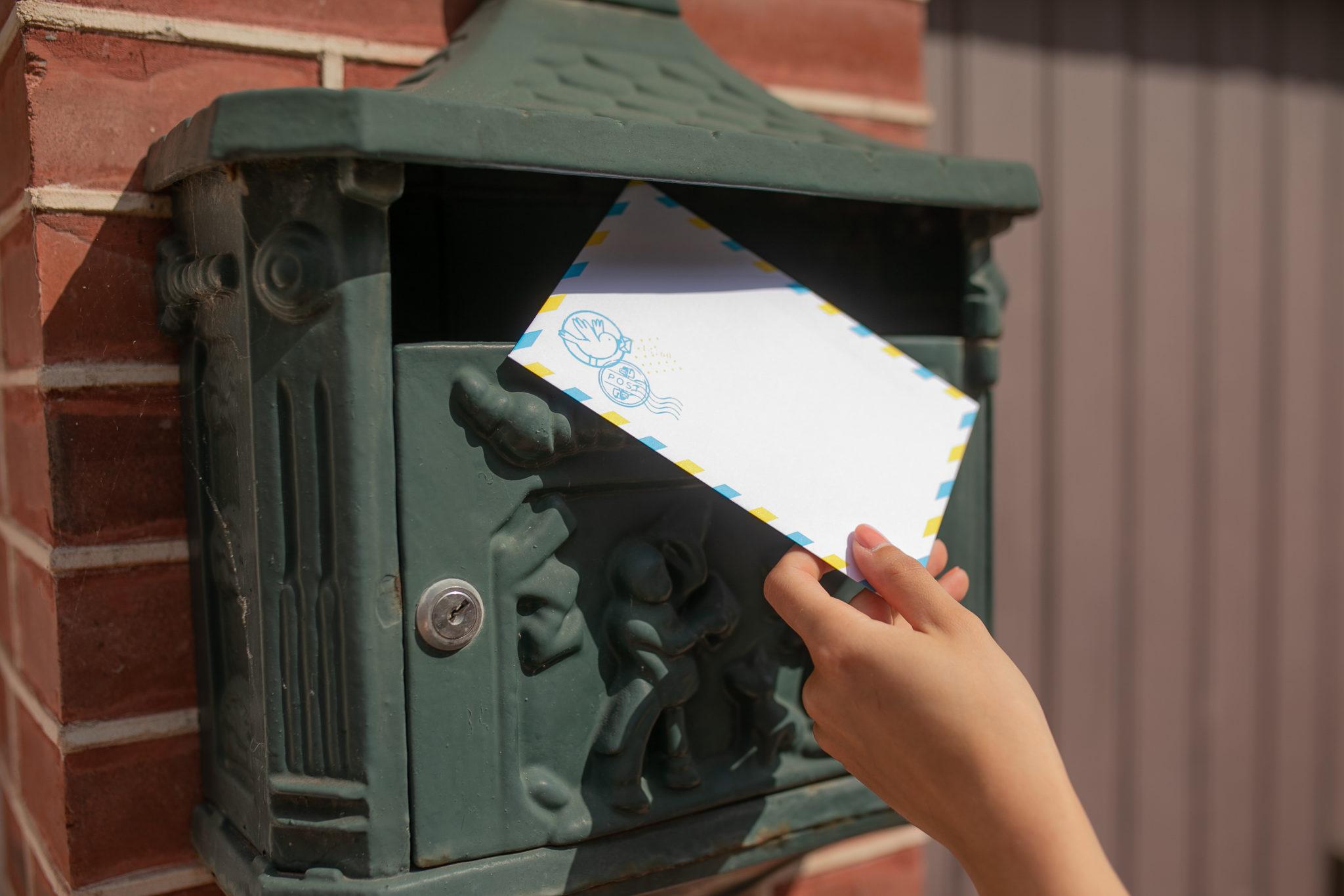 boite aux lettres avec main tenant enveloppe