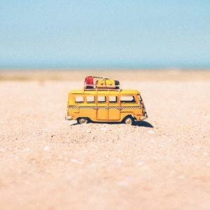 combi van jaune sur sable vacances a la mer