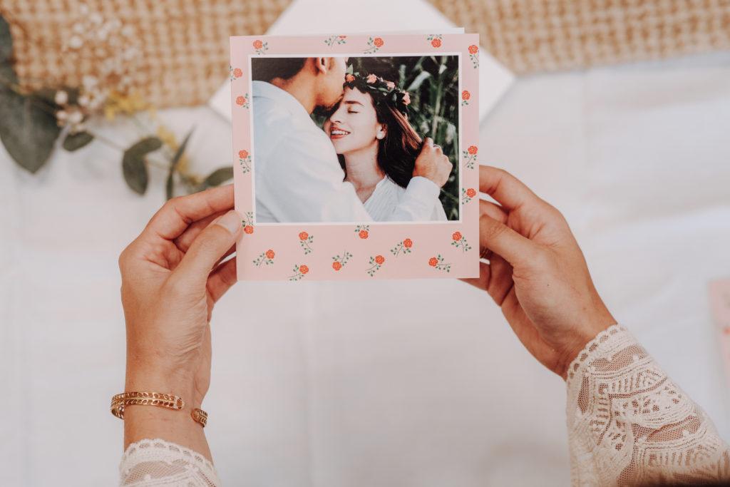 mains tenant carte avec photo couple et fleurs