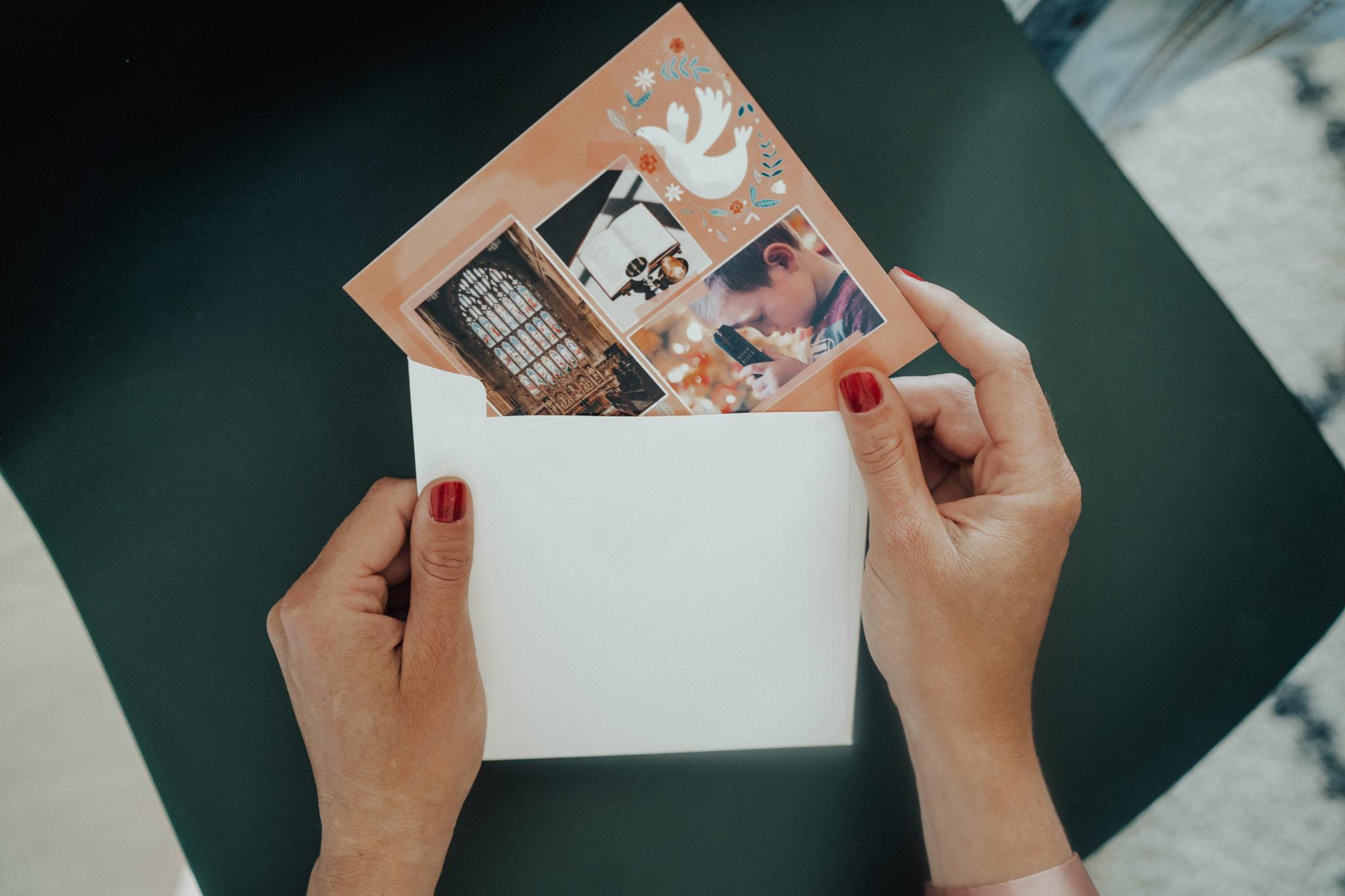 mains sortant une carte de bapteme d'une enveloppe