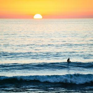 Surfeur sur le spot de surf de Hossegor en France au coucher du soleil
