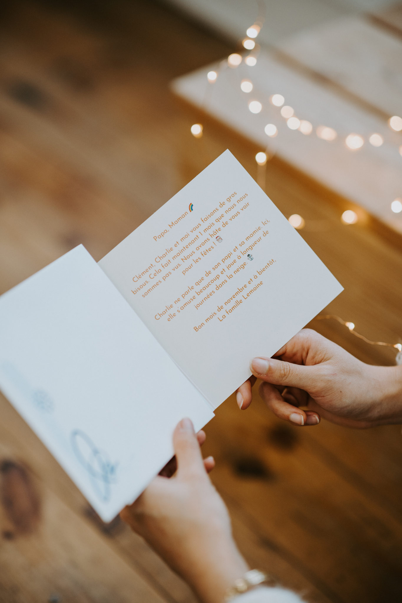 hands opening a card with message and fairy lights
